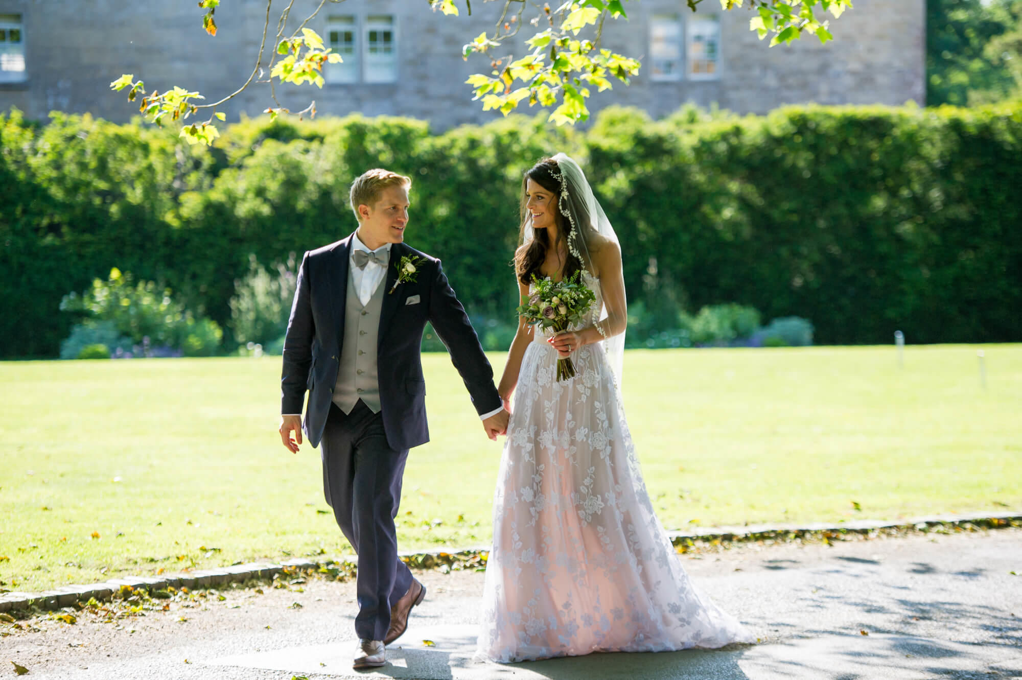 bride and groom holding hands walking on the driveway at babington house