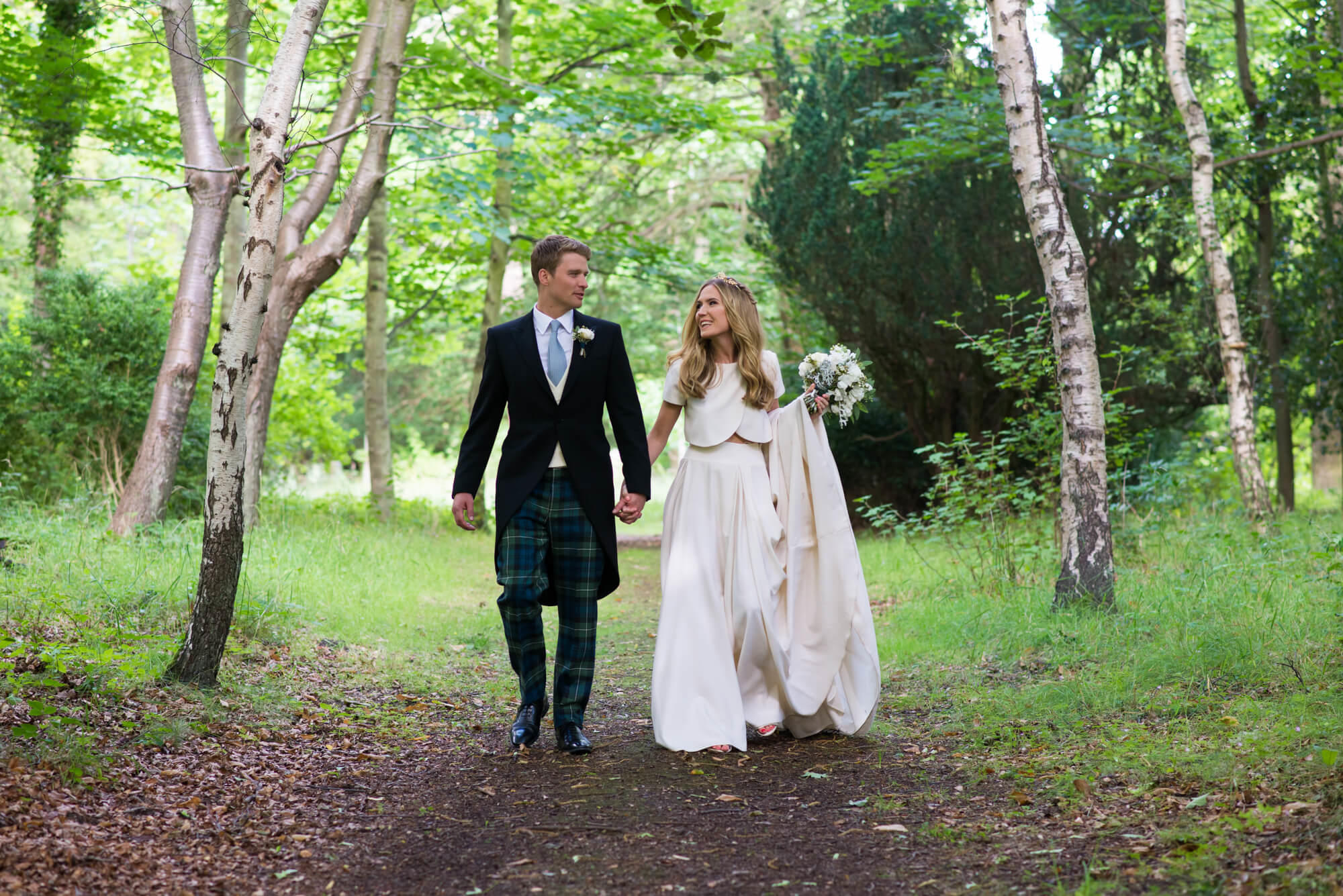bride and groom walking in the woods at Gosford House wedding in Scotland by Especially Amy wedding photography