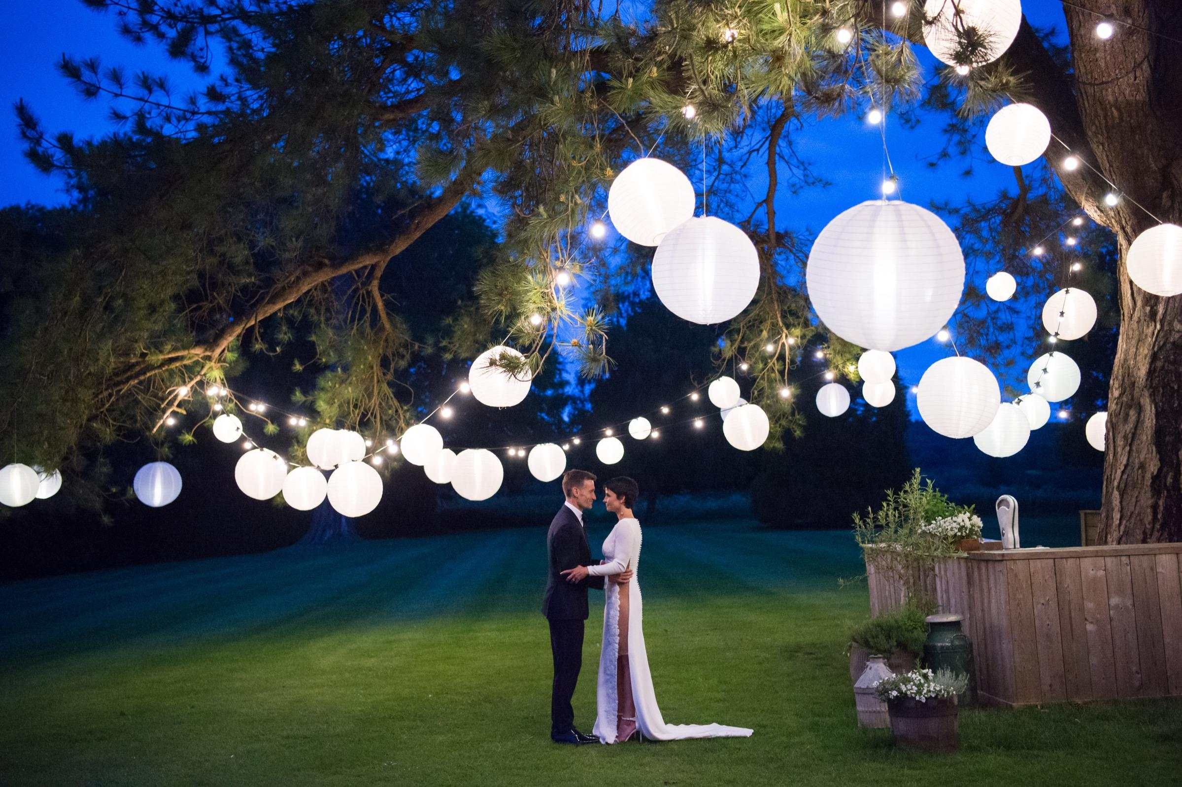 A bride and groom in the gardens of babington house at nighttime