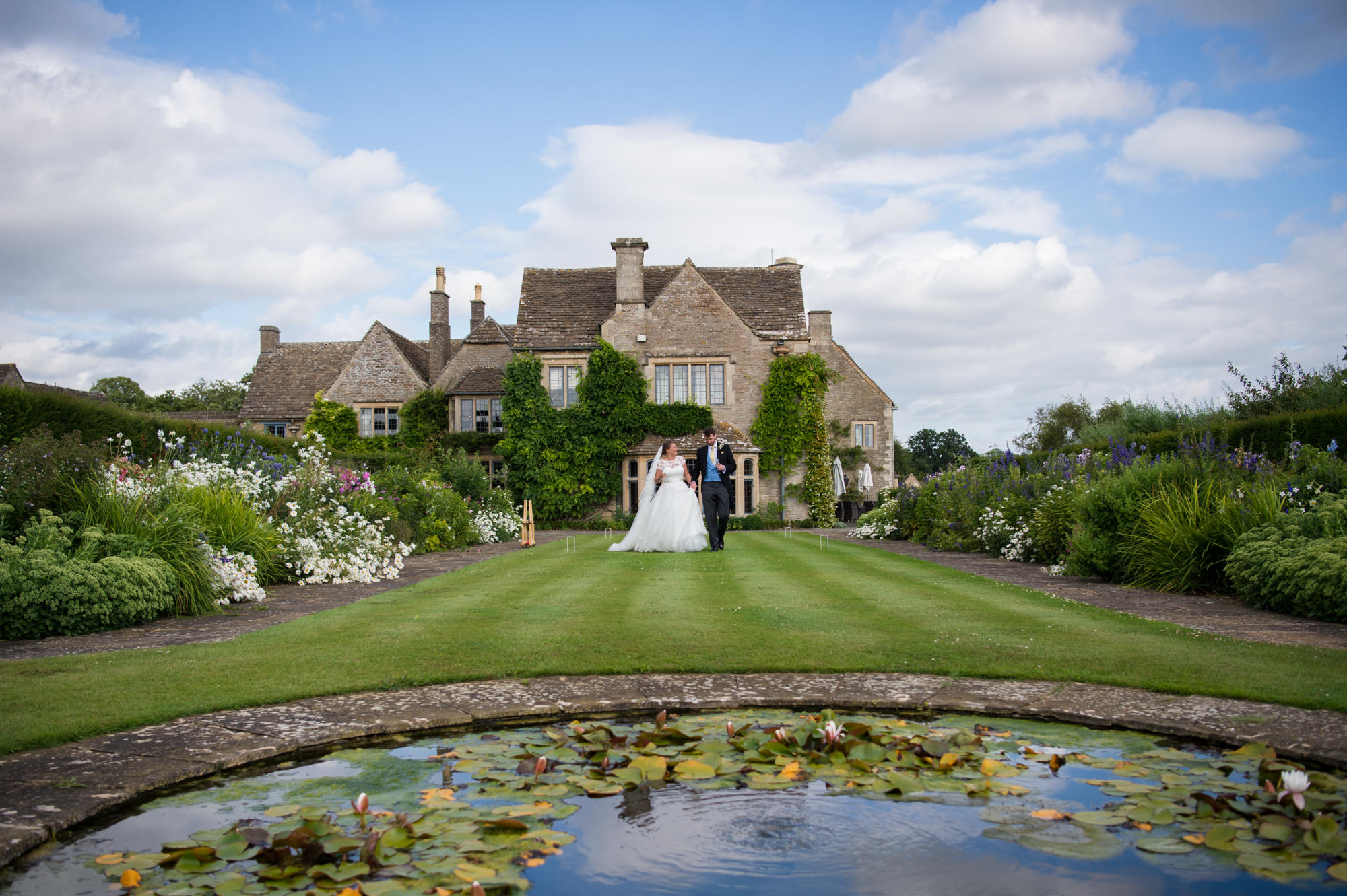 Bride and groom walking in the gardens of Whatley Manor with the wedding venue in the background