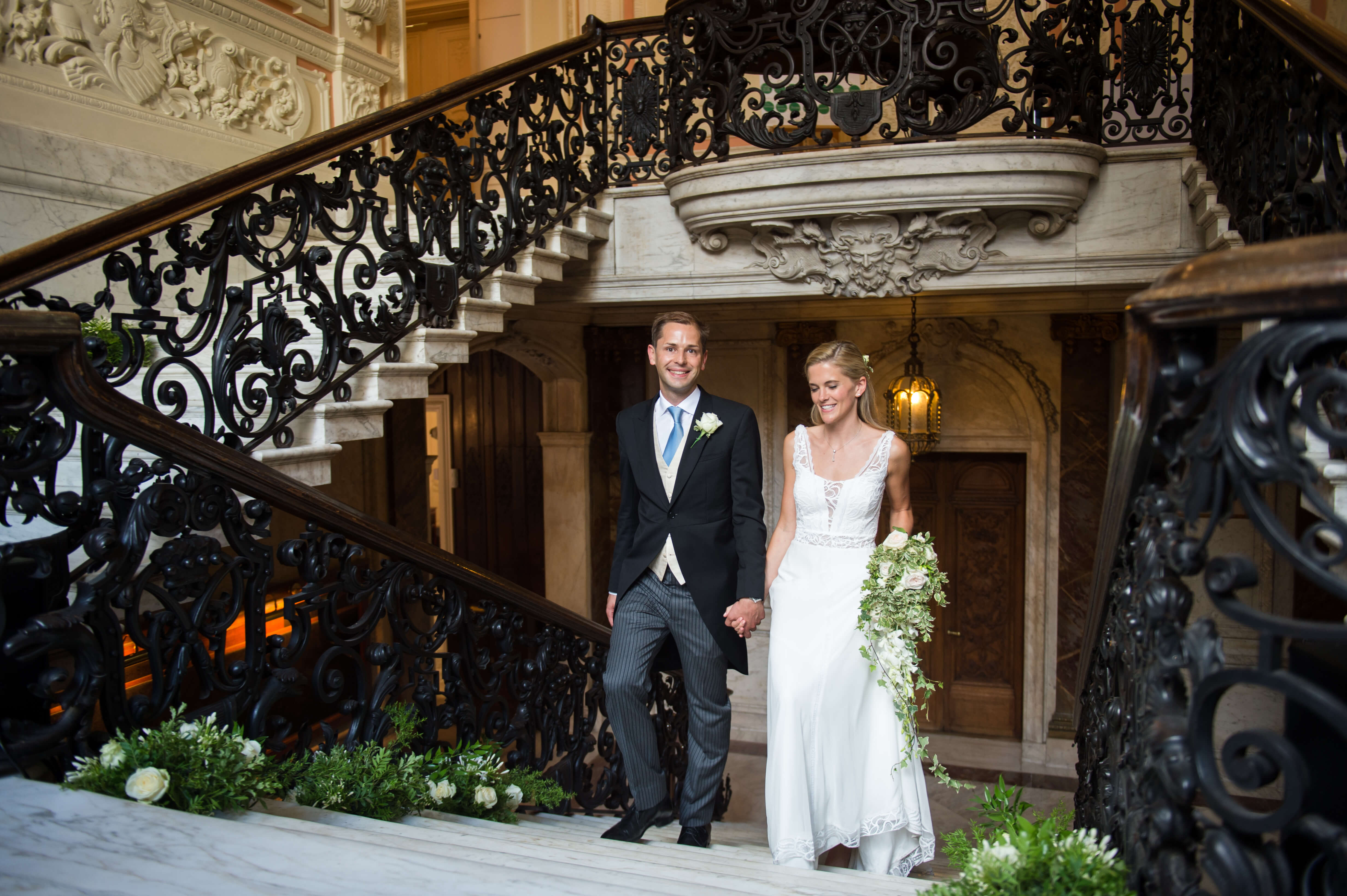 bride and groom on the stairs at dartmouth house wedding venue in mayfair london