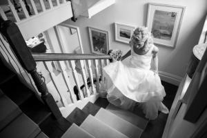 a black and white photograph of a bride coming up the stairs in her wedding gown