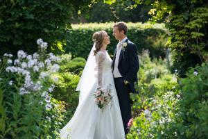 a bride and groom in the gardens of chenies manor house after their wedding