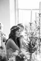 a bride wearing a floral tiara listening to a wedding speech