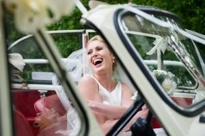 a bride laughing in her open top vintage wedding car