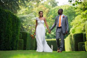 a bride and groom walking through an english country garden after their wedding