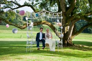 bride and groom on a vintage swing at bocconnoc wedding venue in cornwall