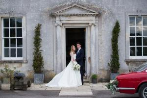 bride and groom standing outside a country house wedding venue
