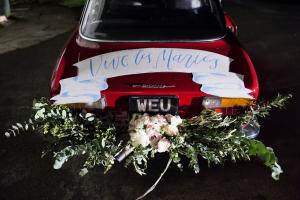 a vintage red car with beautiful wedding flowers