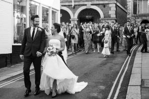 bride and groom walking down the street outside rye town hall and the george in rye