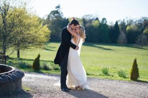bride and groom enjoying a kiss at botleys manor in surrey before the wedding breakfast begins