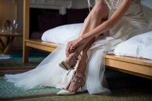 bride putting on her Louboutin bridal shoes at cowley manor