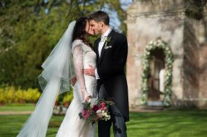 couple kissing at babington house wedding with floral bouquet by passion and a lace wedding gown
